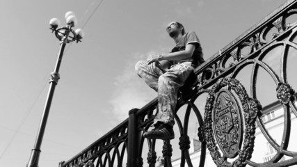 Young man sitting on the fence. Black and white
