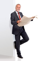 Mature business man with newspaper, leaning against a wall