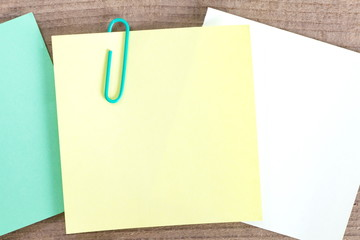 Blank paper note and clip on wood background