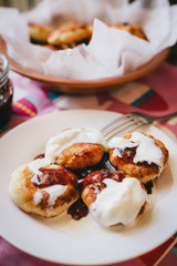 Homemade cottage cheese pancakes with jam and creamy sauce