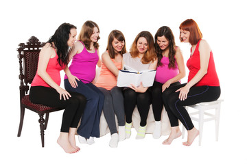 six smiling pregnant women sitting and reading a book