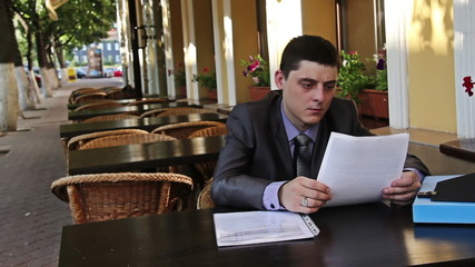 Businessman works with documents in the cafe
