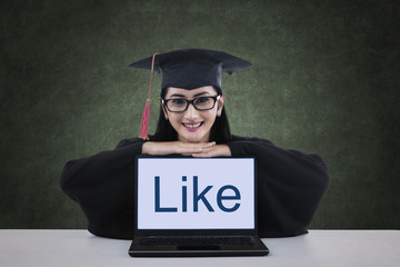 A female graduate showing like on laptop screen
