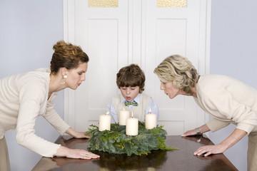 Mutter,Großmutter und Enkel ( 4-7) bläst Adventskranz
