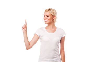 Young smiling woman with white t-shirt pointing up at copy space