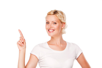 smiling woman with blank white t-shirt pointing up at copy space