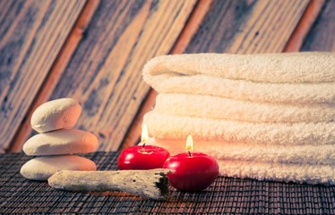 Spa massage with towel stacked stone and red candles