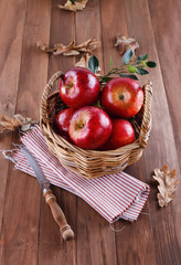 Red apples in a woven basket on wooden background