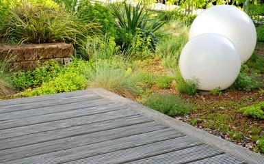 Garten mit Holzterrasse und Lampen