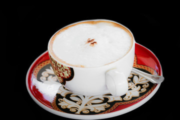A cup of cappuccino on black background