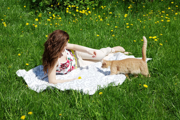 The girl with a cat lies on a green grass