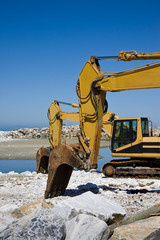 Yellow diggers on the seashore building a breakwater