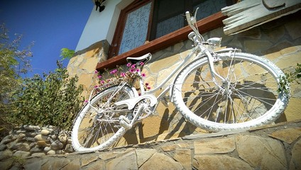 White bicycle decorated with colorful flowers
