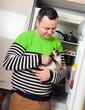 guy with kitten near  refrigerator