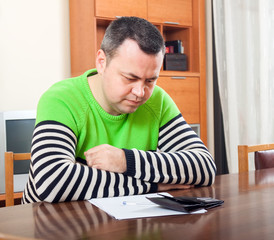 sad man filling financial documents