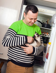 guy with kitten near  refrigerator