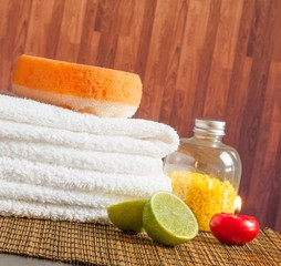 Spa massage with towel stacked red candle and lime