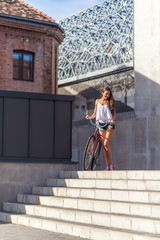 Beautiful woman with old bike in front of the city building