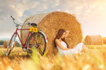 Fashion photo, beautiful woman cycling in a wheat field