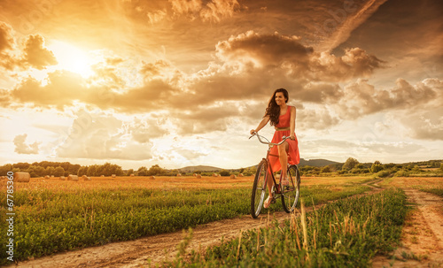 canvas print picture Beautiful woman with old bike in a wheat field