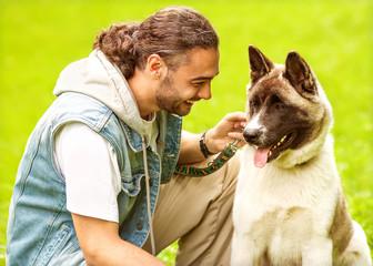 Man and Akita Inu dog  walk in the park.