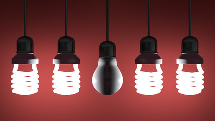 Dead tungsten light bulb hanging among glowing spiral ones