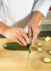 Chef cutting the courgette closeup