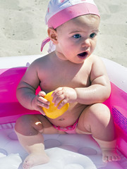 Happy baby girl playing in an inflatable pool on the beach