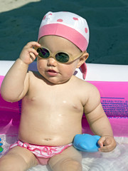 baby girl takes off   sunglasses inside an inflatable pool on th