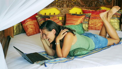 Woman watching funny film on laptop on oriental bed