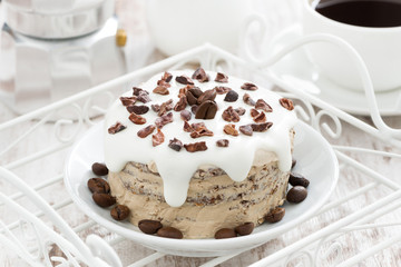 coffee cake with icing decorated with cocoa beans on a plate