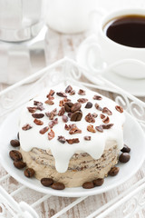 coffee cake with icing decorated with cocoa beans, top view