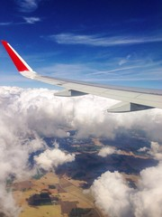 Plane wing against clouds and blue sky.