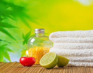 Spa massage ith towel stacked,red candle and lime