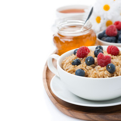 oat porridge with fresh berries and honey, black tea, isolated