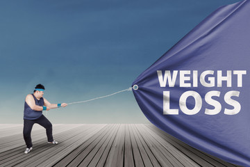 Fat man pulling a weight loss banner 1