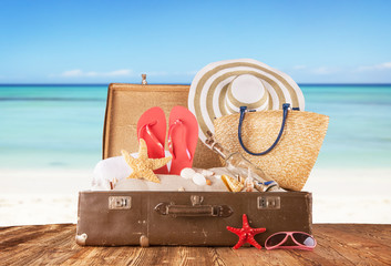 Old suitcase with accessories on beach