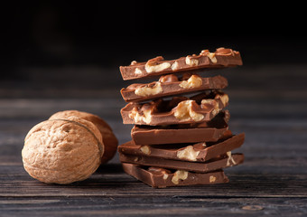 Chocolate with nuts on wooden background