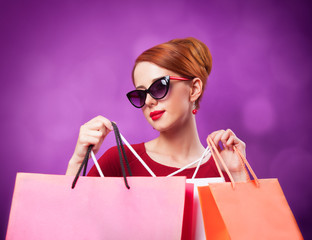 Redhead women with shopping bags on purple background.