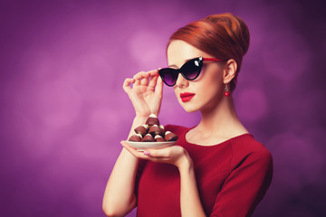 Redhead women with candy on violet background.