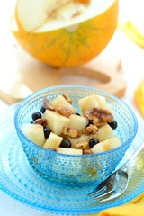 Fruit dessert made of melon, blueberries and caramelized nuts .