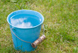 Blue bucket of water on grass - 67794941