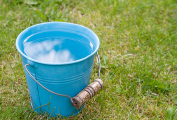 Blue bucket of water on grass