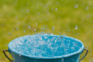 Rain falling into full bucket of water