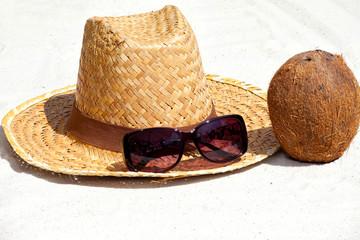 Kokosnuss und Strohhut am Strand