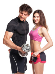 Athletic man and woman with dumbbells on the white background