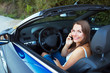 Smiling woman talking on phone in a cabriolet car
