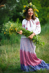 Young smiling girl in Ukrainian costume with a wreath on his hea