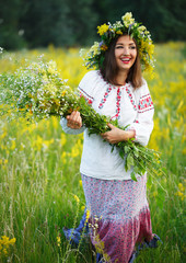 Smiling girl in Ukrainian costume with a wreath on his head in a