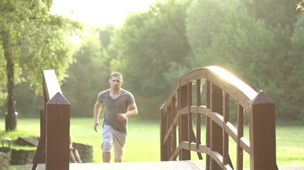 Man jogging across bridge in park, super slow motion, 240fps